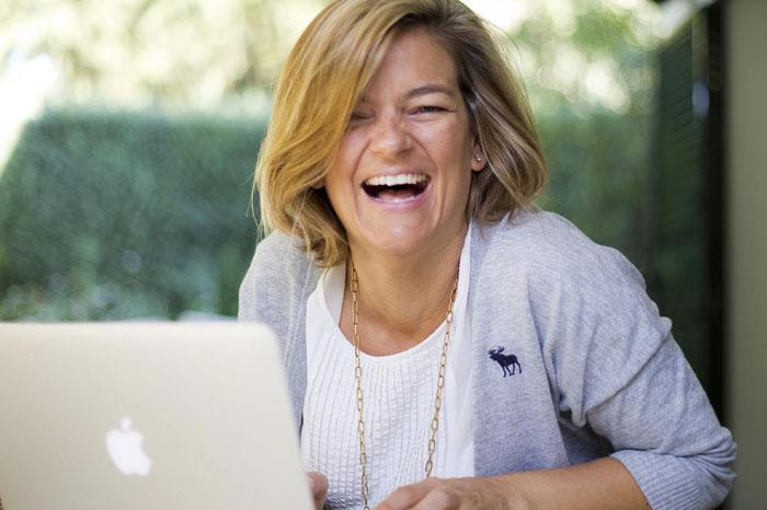 Pepa sonriendo delante de un Mac